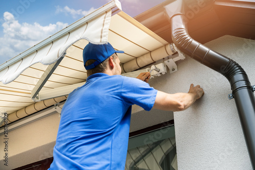Fotografie, Obraz  man installing awning on house facade wall over the balcony window