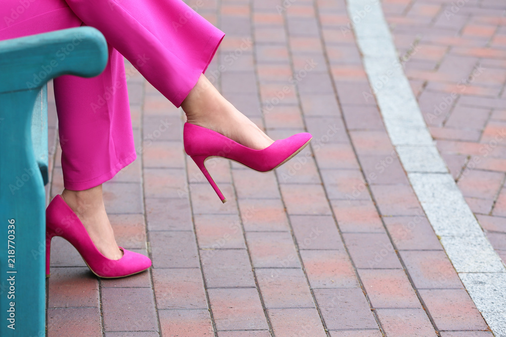 Fototapety, obrazy: Young woman in stylish high-heeled shoes resting on bench outdoors
