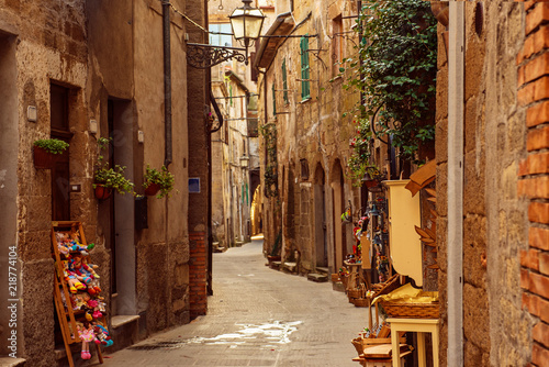 Narrow street of medieval ancient tuff city Pitigliano, travel Italy background Fotobehang