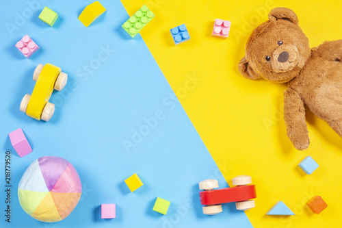 Baby kids toys frame with teddy bear, wooden toy car, colorful bricks on blue and yellow background. Top view