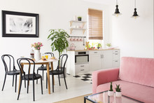Pink Sofa In White Apartment Interior With Kitchenette And Black Chairs At Dining Table. Real Photo