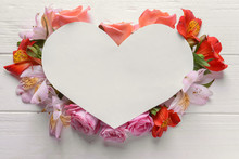 Heart Shaped Sheet Of Paper With Beautiful Flowers On White Wooden Background
