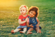 Group Portrait Of Two Cute Adorable Girls Toddlers Children Sitting Together. White Caucasian And Latin Hispanic Babies Hugging Outside In Park. Friendship And Best Friends Forever Concept.