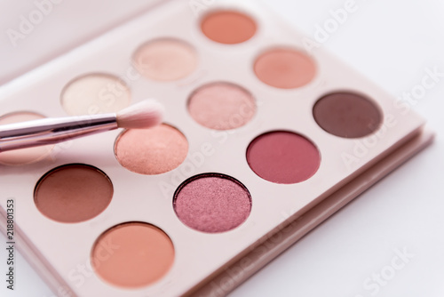 Fotografija soft focus of pink tone eye shadow palette with pink brush