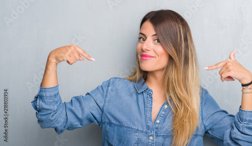 Fotografering Young adult woman over grunge grey wall wearing denim outfit looking confident with smile on face, pointing oneself with fingers proud and happy
