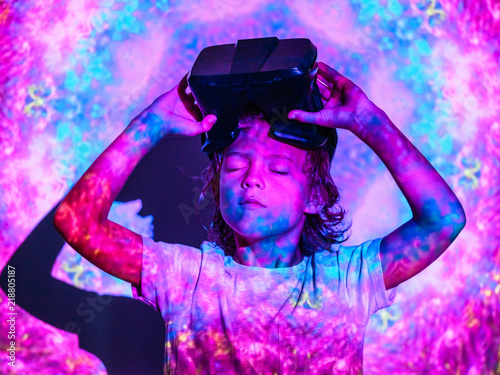 Focused boy with VR glasses under projection