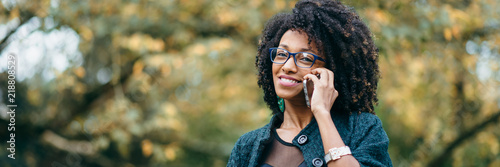 Obraz Happy black woman during a mobile phone call in autumn - fototapety do salonu