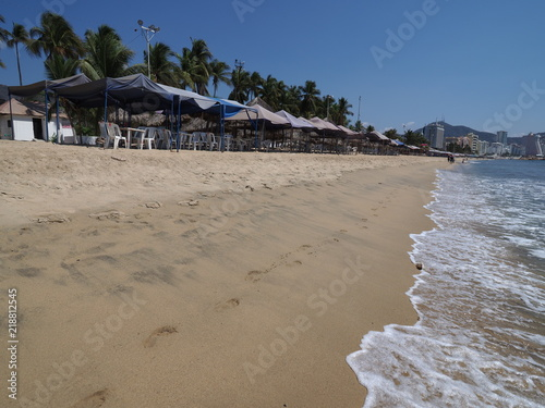 Fotografie, Obraz  Umbrellas and exotic palms on brilliant sandy beach at bay of Acapulco city land
