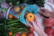 The girl hand is taking vegetables to eco blue bag