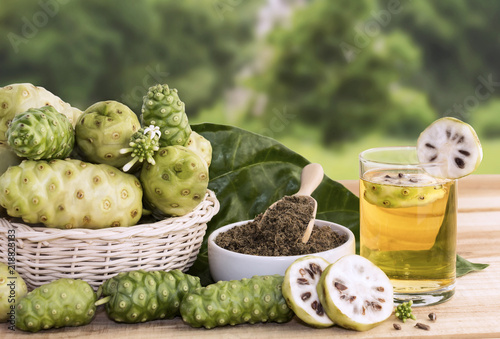 Photo Noni fruit juice or Morinda Citrifolia with noni slice and noni powder for health on the wooden background with copy space for text