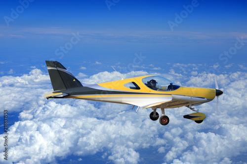 Piękny żółty samolot, awionetka nad chmurami. Wallpaper Mural