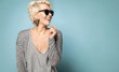 Leinwanddruck Bild - Attractive blonde in stylish clothes and sunglasses. Lovely female laughing and looking away. Copy space in right side. Isolated on blue background
