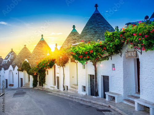 Traditional Trulli houses in Alberobello village, illuminated by sunrise Wallpaper Mural