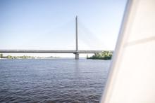 Walk On A Sailing Yacht Along The River. Sail Along The River And Bridge. The Yacht Floats Along The River.