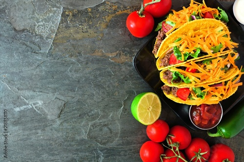 Hard shelled tacos with ground beef, lettuce, tomatoes and cheese. Top view, corner border on a dark background with copy space.
