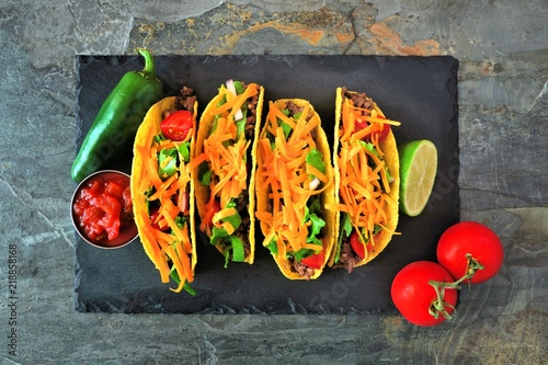 Hard shelled tacos with ground beef, lettuce, tomatoes and cheese. Above view on a dark background.