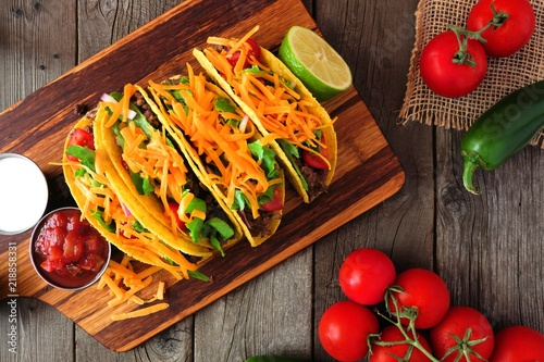 Traditional hard shelled tacos with ground beef, lettuce, tomatoes and cheese. Top view table scene against a rustic wood background,