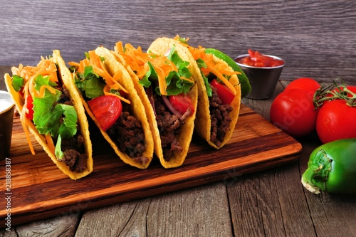 Hard shelled tacos with ground beef, lettuce, tomatoes and cheese. Table scene with a rustic wood background.
