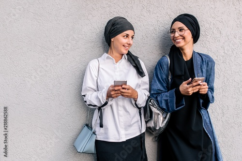 Muslim hijab women communicate on social networks through the phone looking at each other