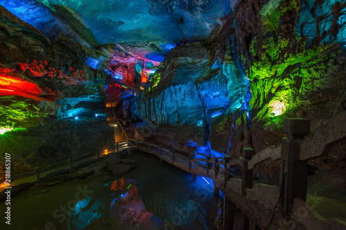 Abstract cave interior chamber photograph - colored lights, bumpy rock surfaces and exotic rock formations. Textures, rugged surface, underground exploration. Alien planet concept, cave geology.