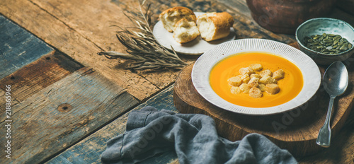 Obraz na plátne Fall warming pumpkin cream soup with croutons and seeds on board over rustic wooden background, copy space, wide composition