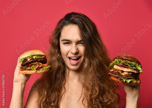 Fotografiet Woman hold two burgers sandwich in hands compare with hungry mouth on pink red b