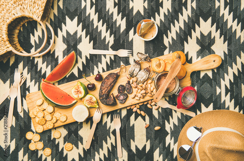 Keuken foto achterwand Summer picnic setting. Flat-lay of fresh fruit, smoked sausage, nuts, cheese, pate and cracker on wooden board over linen blanket background, top view. Outdoor gathering or lunch concept