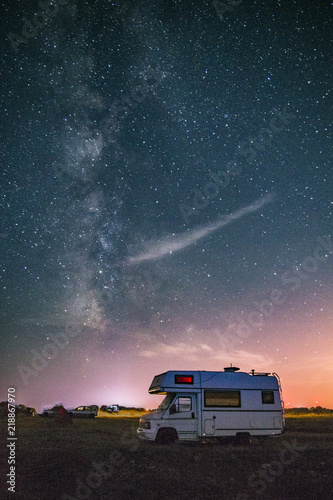 Camper van camping with the Milky way in the background Wallpaper Mural