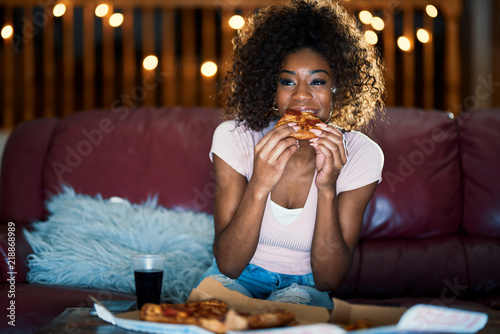 Fototapeta woman eating pizza and watching tv late at night on sofa obraz