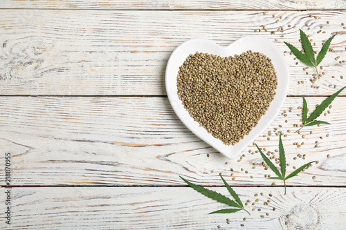 Flat lay composition with hemp seeds and space for text on wooden background
