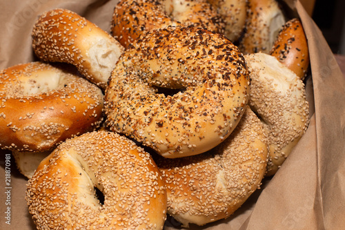 Variety of assorted authentic New York style Bagels with seeds in a brown paper bag.