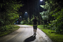 Alone Young Man In Casual Walking On The Night Forest Road With The Street Lights