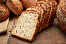 Heap Of Whole And Sliced Fresh Baked Bread On Wooden Background