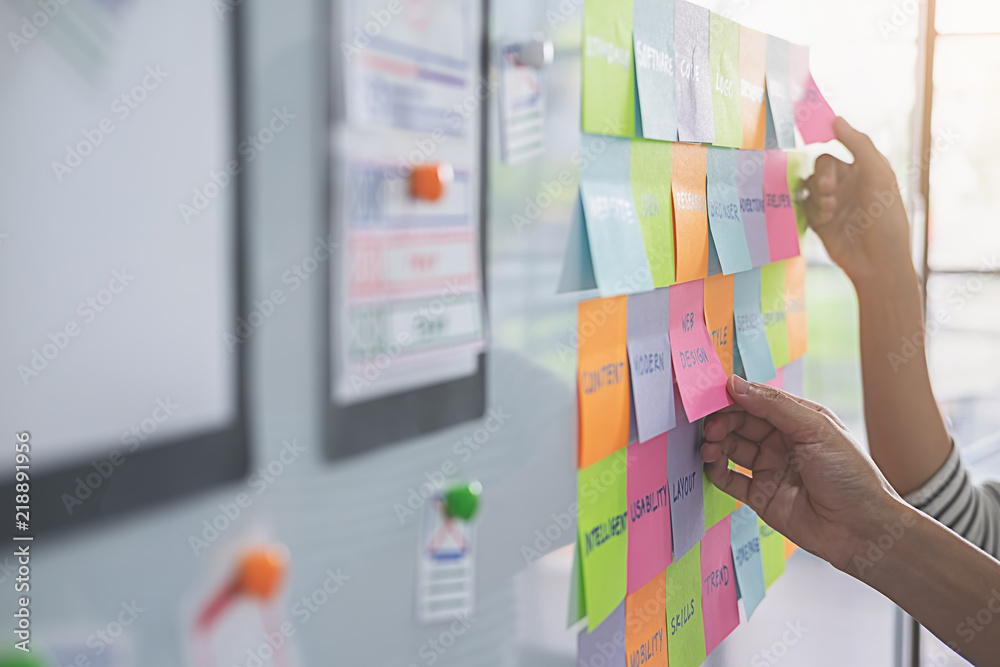 Fototapeta Web designer brainstorming for a strategy plan. Colorful sticky notes with things to do on office board. User experience (UX) concept.
