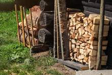 Stack Of Firewood Next To Old Wooden Cottage Wall, Sun Lit Grass Lawn In Front Of It.