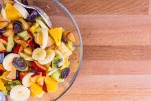 Fruit And Berry Salad In A Glass Bowl On A Wooden Board - Copy Space