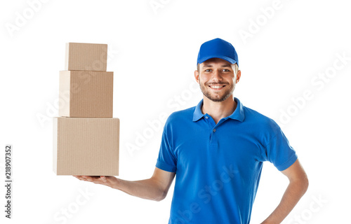 Fotografía  Smiling delivery man holding pile of cardboard boxes