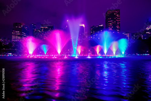 Foto auf AluDibond Violett The colorful of fountain on the lake at night, near by Twin Towers; with city on background. Kuala Lumpur, Malaysia.