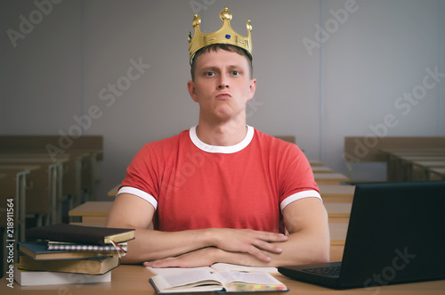Photo Arrogant student boy with golden crown above his head with an insolent look sits at a desk