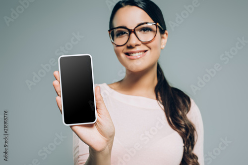 Fototapeta young woman showing smartphone with blank screen, isolated on grey obraz