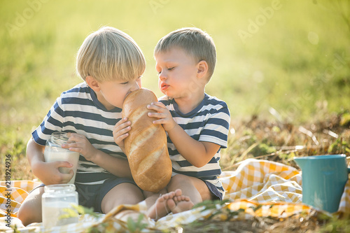 Cuadros en Lienzo Cheerful children drinking fresh milk outdoors
