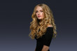 Leinwanddruck Bild - Blonde hairstyle woman beauty with long curly blonde hair over dark background