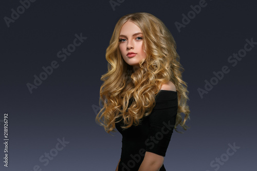 Stampa su Tela Blonde hairstyle woman beauty with long curly blonde hair over dark background