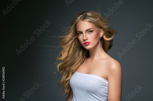 Fényképezés  Blonde hairstyle woman beauty with long curly blonde hair over dark background