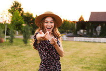 Photo Of Beautiful Young Woman 20s Wearing Dress And Straw Hat Smiling, And Inviting To Follow Her With Hand Gestures While Walking Outdoor In Countryside