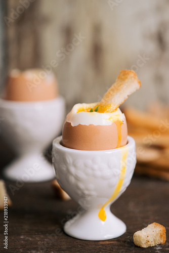 Fotografía  The yolk flows from boiled egg on toast