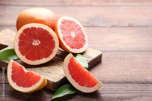 Ripe grapefruits with green leafs on brown wooden table