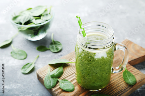 Spinach smoothie in glass jar on grey wooden table