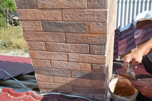 Installing House Chimney Blocks On The Rooftop. Roofer Decorate And Protecting Chimney Bricklaing.