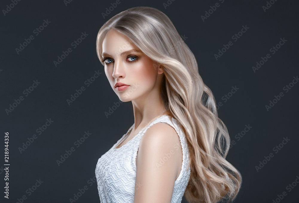 Fototapeta Amazing woman portrait. Beautiful girl with long wavy hair. Blonde model with hairstyle over black background
